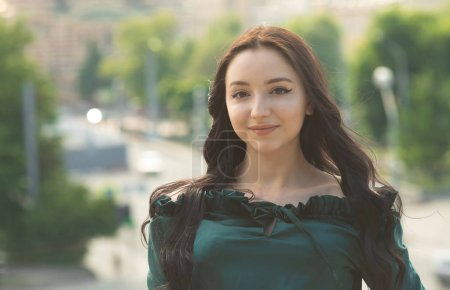 Photo for Beautiful young brunette woman smiling at camera in park - Royalty Free Image