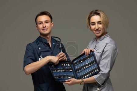 Photo pour Deux médecins tenant des ampoules avec des vaccins sur fond gris, gros plan. Objets médicaux. - image libre de droit