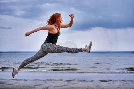 Photo pour Une femme d'âge moyen aux cheveux roux saute en faisant du jogging. Une femme pratique la gymnastique sur le rivage sablonneux d'une grande rivière. Matin de printemps nuageux . - image libre de droit