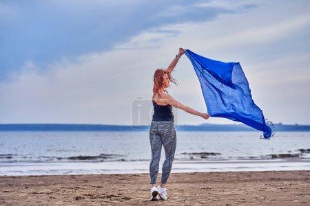 Photo pour Slim rousse femme d'âge moyen dans la forme sportive est engagée dans la danse avec une écharpe bleue. Une femme est engagée sur le rivage sablonneux d'une grande rivière. Matin d'été nuageux . - image libre de droit