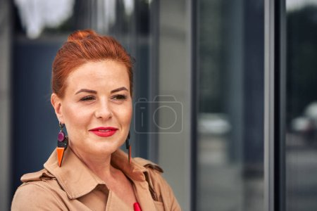 Photo for Portrait of a red-haired middle-aged woman in a brown cloak  while walking around the city. Cloudy summer evening. Close-up. - Royalty Free Image