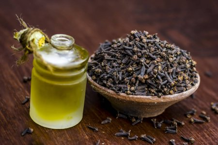 raw cloves in a clay bowl with its oil beneficial for skin care and health care