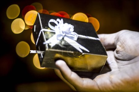 A hand holding gift box, close up view