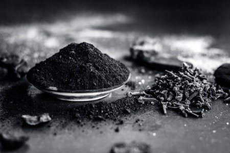 Traditional ingredients of toothpaste with coal,cloves and salt, sodium chloride on a wooden surface.