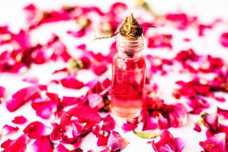 Photo pour Pétales de rose étalés sur la surface avec une petite bouteille en verre de concentration essentielle de rose ou d'essence sur elle . - image libre de droit