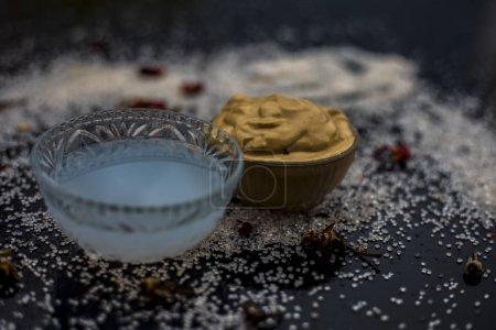 Photo pour Masque facial composé de multani mitti et huile de noix de coco pour le traitement du bronzage dans des bols sur la surface en bois - image libre de droit