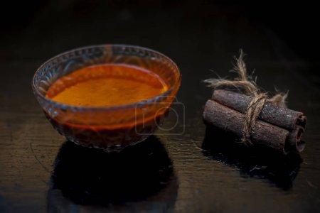Masque capillaire cannelle et miel dans un bol en verre sur une surface en bois avec des lumières dorées isolées. Avec du bâton de cannelle cru et du miel présent à la surface .