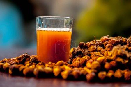 Photo pour Plan rapproché de la noix de savon crue fraîche à la surface brune avec sa solution ou son liquide dans un verre à côté. - image libre de droit