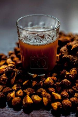 Photo pour Plan rapproché de la noix de savon crue fraîche sur la surface brune avec sa solution ou son liquide dans un verre à côté. - image libre de droit