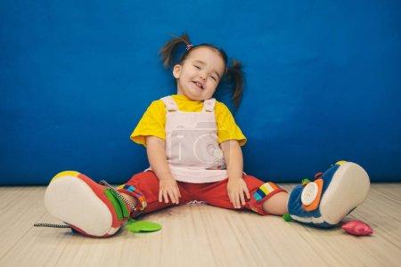 Photo pour Une petite fille avec deux queues et des énormes chaussures assis sur le sol - image libre de droit
