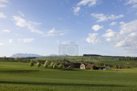 Photo for Farm in central Switzerland on a sunny spring day near Nottwil. In the background Mount Pilatus - Royalty Free Image