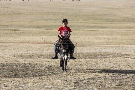 Photo pour Song Kul, Kirghizistan, 8 août 2018: Un garçon dans un T-shirt rouge chevauche un âne à travers la steppe au lac Kul chanson au Kirghizistan - image libre de droit