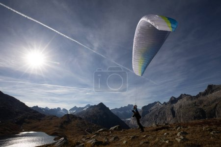 Photo for Paraglider Pilot stands on a slope and balances his paraglider above his head in the Alps of Switzerland - Royalty Free Image