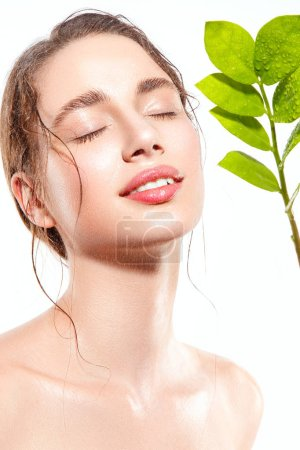 Photo for Beautiful woman portrait with fresh wet skin and green plant. - Royalty Free Image