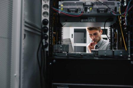 Photo pour Jeune homme d'affaires beau engeneer dans la salle de serveur de datacenter - image libre de droit