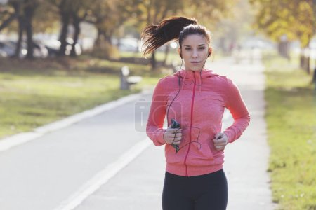 Female runner jogging and listening to music on the street