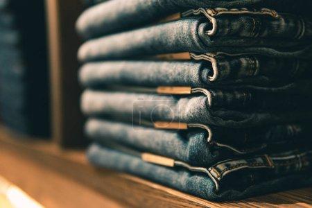 Photo pour Jeans empilés avec plusieurs tailles de taille sur les étagères ou les placards et mise au point sélective. - image libre de droit