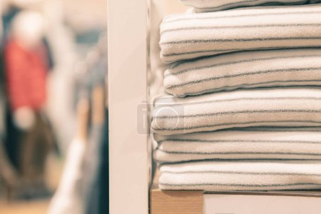 Photo for Stacked white clothing that has many sizes on the shelf or closets or clothing store. - Royalty Free Image