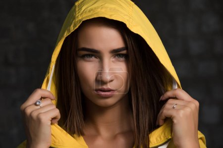 Photo pour Portrait de femme sérieuse confiant sous capuche jaune - image libre de droit