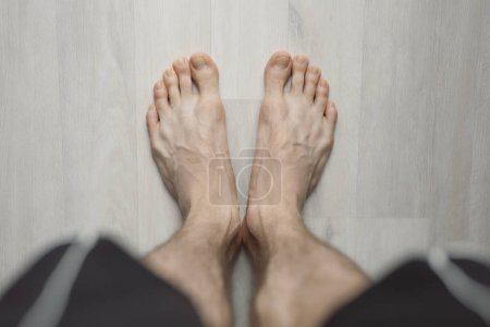 Photo for POV, man barefoot on the floor, male legs - Royalty Free Image