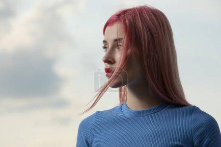 Photo pour Bizarre belle femme aux cheveux roses sur fond de ciel, portrait d'art créatif - image libre de droit