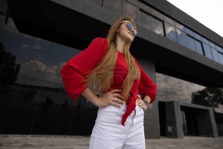 Photo for Fashion model in red blouse posing on city street wearing sunglasses - Royalty Free Image