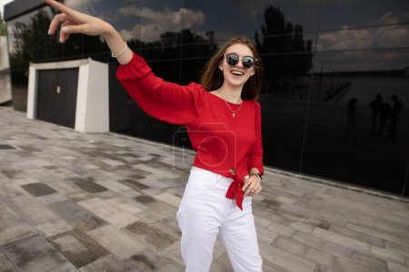 Photo for Fashion model in red blouse showing something on city street - Royalty Free Image