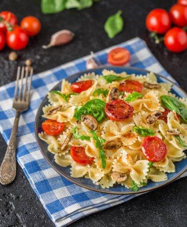 Photo pour Pâtes italiennes traditionnelles aux champignons, tomates cerises rôties et feuilles de basilic sur fond de pierre noire avec serviette à carreaux - image libre de droit