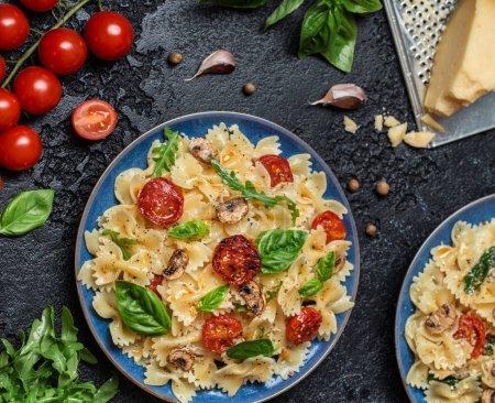 Photo pour Pâtes italiennes traditionnelles aux champignons, tomates cerises rôties et feuilles de basilic sur fond de pierre noire - image libre de droit