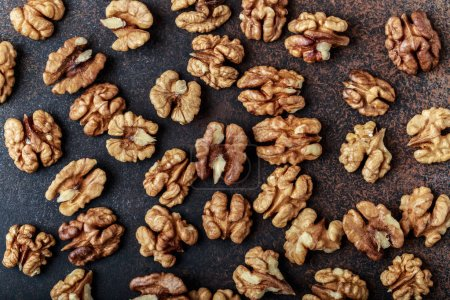 Top view of dry walnut kernels on dark stone background