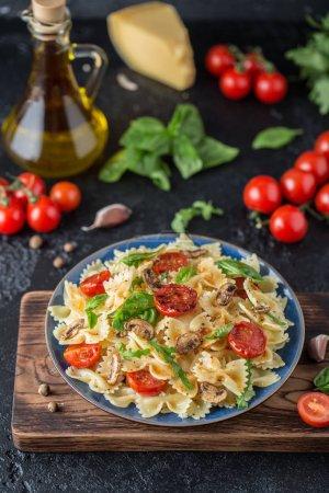 Photo pour Pâtes italiennes traditionnelles aux champignons, tomates cerises rôties et feuilles de basilic sur planche à découper en bois - image libre de droit