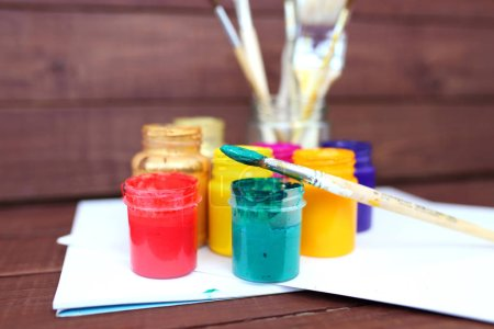 Colorful acrylic paints with paint brushes on wooden background in art-studio