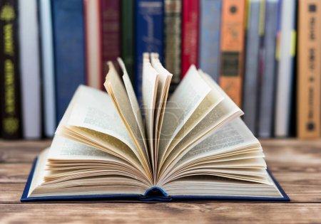 Photo pour Un livre ouvert sur la table en bois avec pile de vieux livres sur fond - image libre de droit