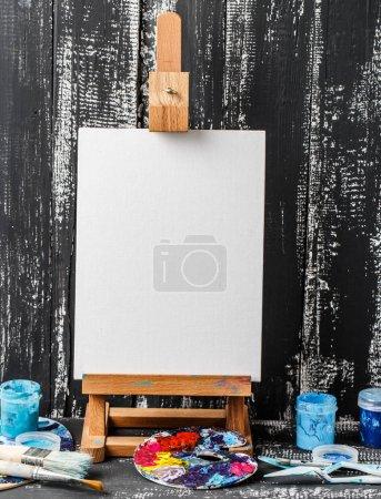 Photo pour Petit chevalet vierge avec peintures et pinceaux sur fond bois grunge - image libre de droit