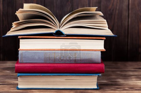 Photo for Old open book on stack on vintage books on wooden background - Royalty Free Image