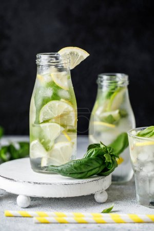 Photo pour Citronnade au basilic d'été sur fond gris. Cocktail d'été frais avec basilic, citron et glaçons. Citronnade fraîche maison au citron et basilic. Concept d'aliments et boissons - image libre de droit
