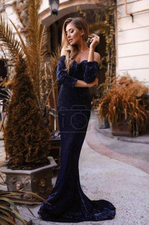 Photo pour Belle femme en robe fantaisie, marchant dans la rue, mode, beauté, maquillage, robe de soirée, fille souriante, mannequin posant, port de luxe, accessoires, blonde, cheveux volumineux, rouge à lèvres, yeux, corps parfait, cheveux longs, style - image libre de droit