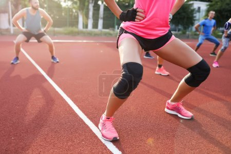 Photo for Woman doing sit-ups on the training, healthy, fresh, sun rise, summer, sport,  sportwear, sneakers, activity, fitness, lifestyle, outdoor, stadium - Royalty Free Image