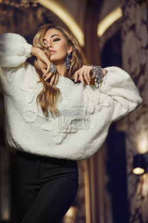 Photo for Elegant tender woman with blonde curly hair standin, raised her hands to the face, fashionable look. Wearing white warm sweater and black skirt, classic colors. Bright accessories.Makeup and hairstyle - Royalty Free Image