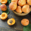 Ripe apricots on a table in a wooden plate, on a s...