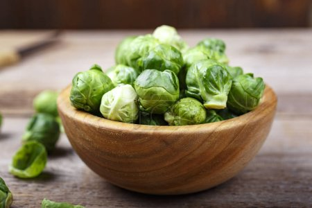 Photo for Brussels sprouts in a wooden plate on a brown wooden backgroun - Royalty Free Image