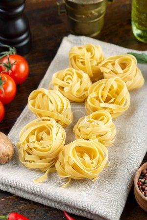 Pâtes de fettuccine fraîches roulées à l'italienne. Concept culinaire italien. Ingrédients pour la fabrication de pâtes. Espace pour ext.