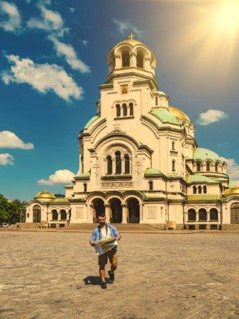 Photo pour Jeune homme caucasien avec une carte visitant la cathédrale Alexander Nevsky à Sofia, Bulgarie par une journée ensoleillée avec éruption solaire. Concept de Wanderlust . - image libre de droit