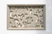 """Постер, картина, фотообои """"Традиционная китайская каменная фреска, изображающая растения на белой стене."""""""