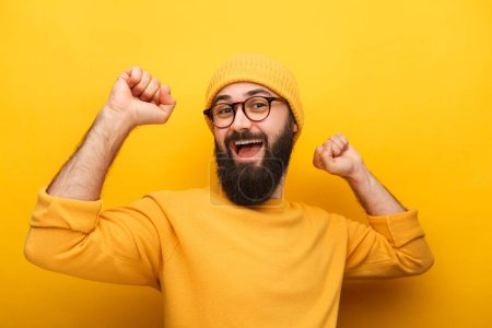 Photo for Stylish bright guy in eyeglasses and yellow outfit smiling at camera posing with hands. - Royalty Free Image