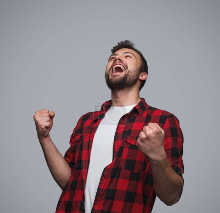 Photo for Trendy man in checkered shirt holding fists up in gesture of success and screaming happily with win on gray background - Royalty Free Image