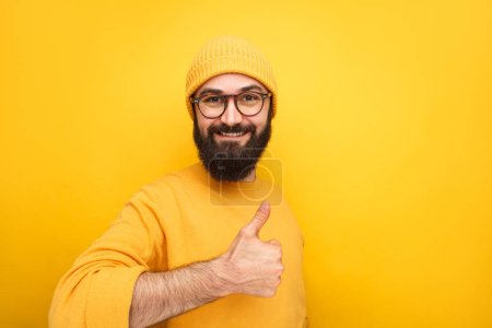 Photo for Happy stylish hipster showing thumb up smiling at camera on yellow backdrop. - Royalty Free Image