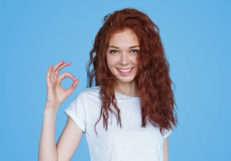 Photo for Pretty young model in white t-shirt showing OK gesture and smiling at camera on blue background - Royalty Free Image