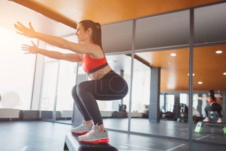 Photo pour De dessous vue latérale de femme sportive gaie faisant squats sur la plate-forme étape dans la salle de gym - image libre de droit