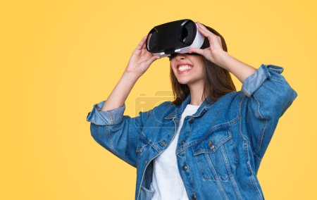 Photo for Trendy teenage woman in denim jacket smiling brightly while wearing modern VR glasses on orange background - Royalty Free Image
